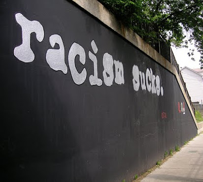 racism sucks painted on a wall