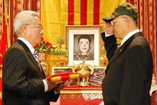 Cựu nghị sĩ Nguyễn Khoa Phước đại diện gia đình nhận Quốc Kỳ từ cựu Chuẩn Tướng Mạch Văn Trường