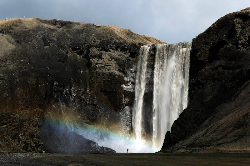 A woman stands near a waterfall that has been dirtied by ash that has accumulated from the plume of an erupting volcano near Eyjafjallajokull, Iceland on April 18, 2010. (REUTERS/Lucas Jackson)