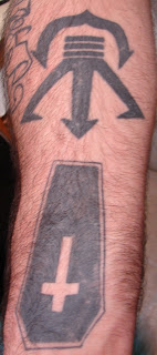 This Arm Tattoo Picture Has A Coffin And A Symbol, Does Anyone Know