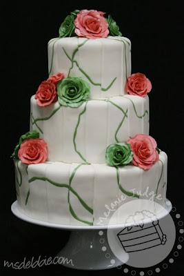 white fondant wedding cake green swirls with green and pink roses