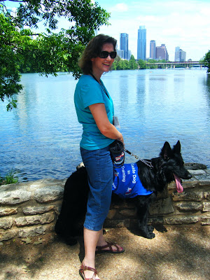 Petey, big black German Shepherd, and I are standing in front of a low stone wall; he's in his work jacket; the water of Town Lake is behind us and the Austin skyline in the background