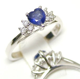 Blue sapphire heart cut stone with three diamonds on either side of it set on white gold.