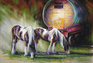 Two horses grazing next to a gypsy caravan wagon