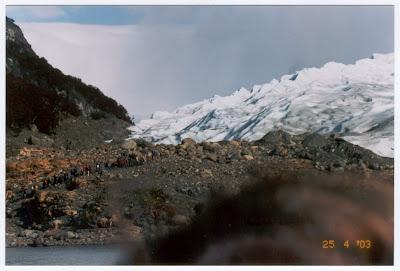 No lado esquerdo da foto, um grupo de pessoas sobe por uma trilha para andar no gelo do glaciar