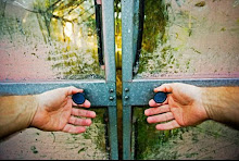 Hands opening door of old glass greenhouse