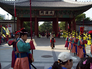 Men in colorful uniforms perorm teh changing of the guard at the palace gate with trumpets and drums