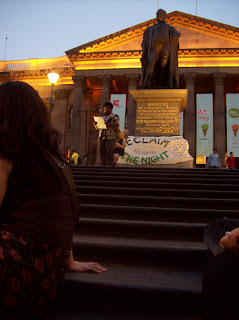 Indigenous speaker stands before the statue of Redmond Barry at night for the rally
