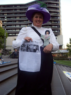 Ursula dressed as a suffragette holding a ceramic suffragette statue she made herself