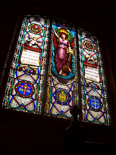 Historic stained glass window depicting Jesus and scrolls about teaching the deaf to speak and understand the Bible