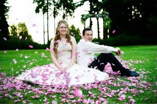 A cute wedding photo with flying rose petals.