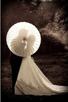 A romantic silhouette wedding couple photograph behind a parasol.