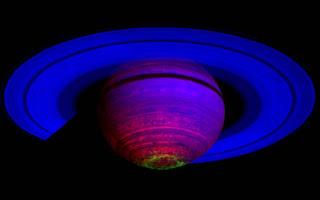 Imagen compuesta de Saturno que muestra completamente al planeta, incluyendo los anillos vistos por la nave Cassini desde el sur. El brillo verde representa las luces de la aurora