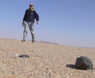 Fotografía del Dr. Peter Jenniskens en Sudán, con algunos de los meteoritos