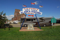 View of the Start of the Alaska Highway Sign Near the Visitor's Center in the Background