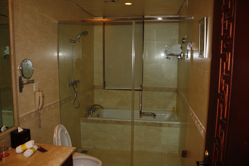 Marble-tiled bathroom, marble tub and shower with glass doors. title=