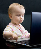 A toddler using a laptop