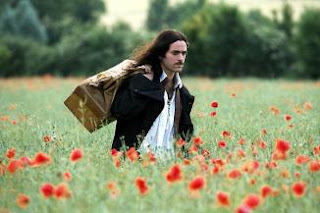Molière storms grumpily through a field of flowers