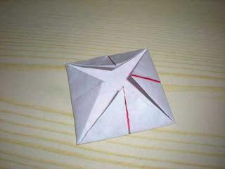Langkah 3: Balikkan kertas lalu lipat sudutnya ke tengah lagi.