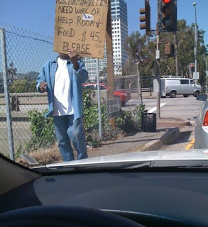 Photo of a man who is homeless with a cardboard sign.