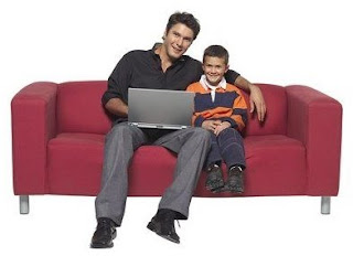 A father and child sitting on a sofa with a computer