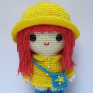 Amigurumi crochet pattern for a girl with a yellow coat.