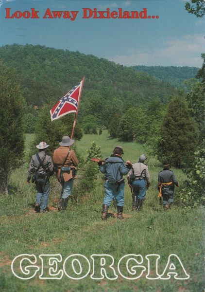 Re-enactment soldiers with confederate flag walking through a valley