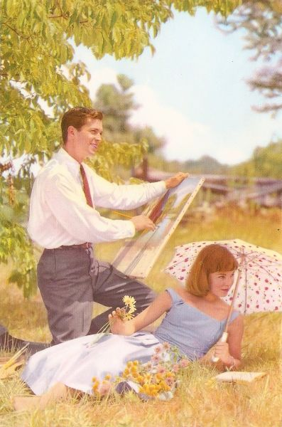 sunny outdoor picture of man painting and woman reclinging on grass
