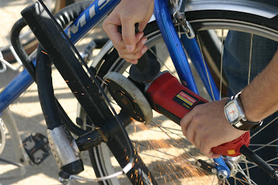 Image of a bike lock being cut by a power grinder