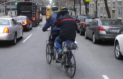 Couple bicycle commuting on a tandem in New York City
