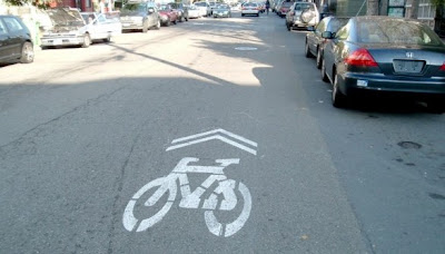 Image of a sharrow road marking, improving safety for bicyclists