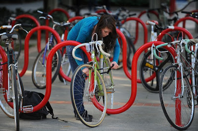 Shawna Sanders, a biology student at Sacramento City College, secures her bike to a rack with a U-shaped lock before heading to class