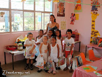 kindergarten schoolchildren with donated school supplies in class