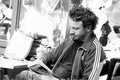 portrait d'un homme lisant un livre à la terrasse d'un café, photo dominique houcmant, goldo graphisme