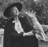 Marianne Moore in cape and hat with cockatoo