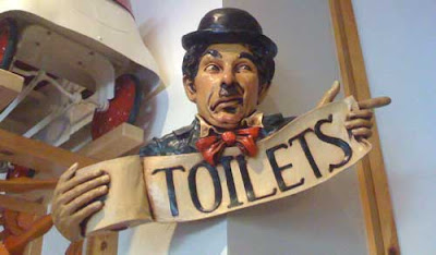Carved Charlie Chaplin holding a role of toilet paper. Letters on the paper read Toilets