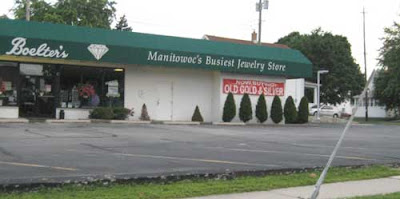 Empty parking lot and boxy store with green awning that reads Manitowoc's Busiest Jewelry Store