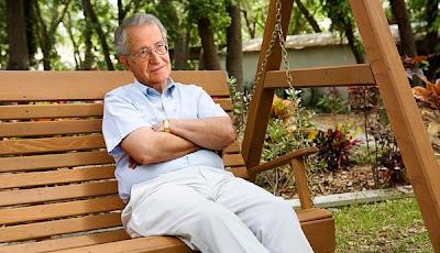 Noam Chomsky sitting on a wooden swing bench
