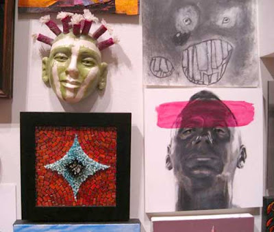 Multiple artworks hung on a wall, two of which depict heads