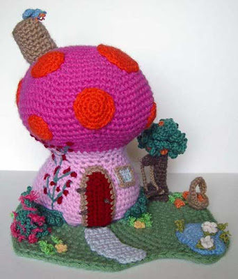 Colorful crocheted mushroom house with landscaping