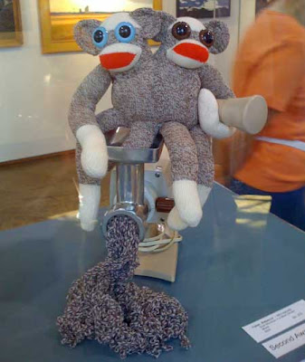Two conjoined sock monkeys, one leg stuck in a meat grinder, brown and white yarn coming out the business end of it