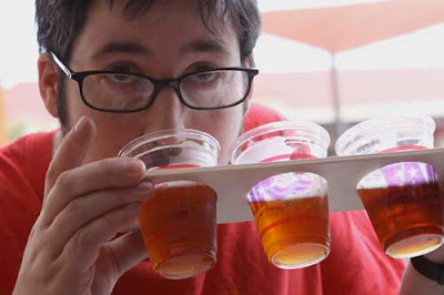 Young man with glasses drinking from a small plastic beer cup, which along with two other cups is embedded in a wooden paddle