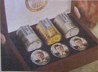 Close up of the brown treasure chest box with three tubes of coins and three coins with color pictures of the Kennedy brothers