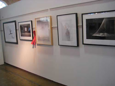 White wall with five works on it, all featuring human nudes