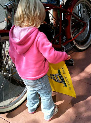 Blond 3-year-old in a pink sweatshirt touching a yellow Don't Tread on Me flag hanging from a bike