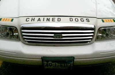 Front end of a white full-sized Ford with the words CHAINED DOGS above the grill
