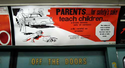 Red, black and white sign warning Parents...for safety's sake teach children, showing a child lying dead in the driveway while dad runs from the car, which just hit him