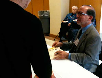 Leonard Marcus preparing to sign a book at a table