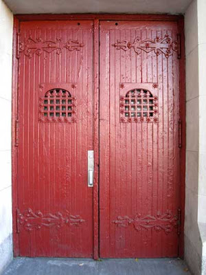 Red-painted doors with metal details as are found on church doors