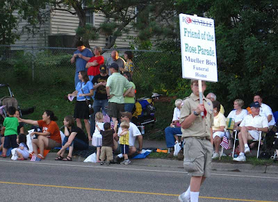 Boy Scout carrying a sign on a stick, reading Rose Parade sponsor Mueller Bies Funeral Home